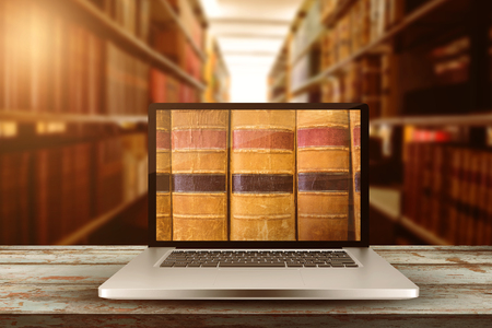 Laptop with with screen against close up of a bookshelf Stock Photo