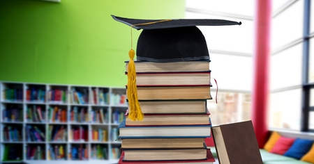 Digital composite of Books and graduation hat in education library Stock Photo
