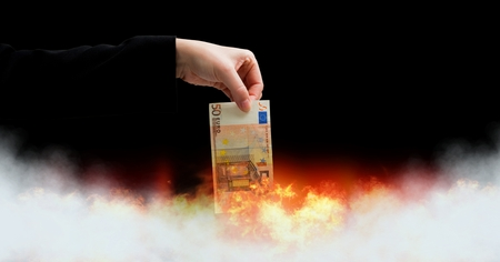 Digital composite of Euro money notes burning in fire
