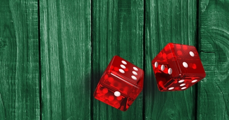 Digital composite of Red dices on wooden green background