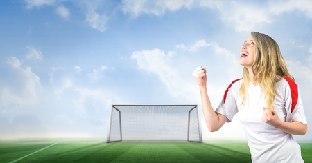 Digital composite of Soccer fan celebrating with fist and goal on pitch