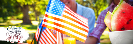 Independence day graphic against cropped image of hand holding american flag Stock Photo