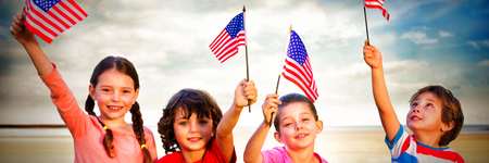 Happy children holding American flags at beach