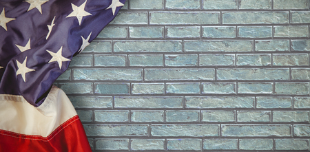 Creased US flag against a stone wall