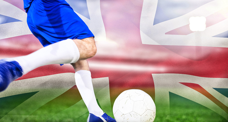 Football player kicking ball against digitally generated great britain national flag Banco de Imagens