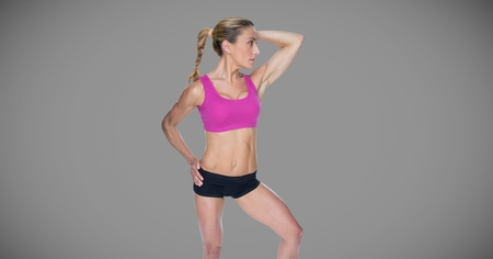 Digital composite of Athletic exercise woman with blank grey background
