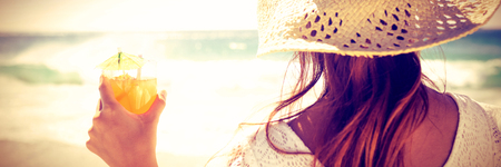Rear view of woman in straw hat holding cocktail at the beach Stock Photo