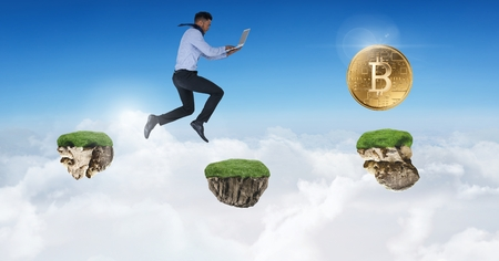 Digital composite of Businessman collecting bitcoins jumping on game platforms in sky holding laptop Stock fotó