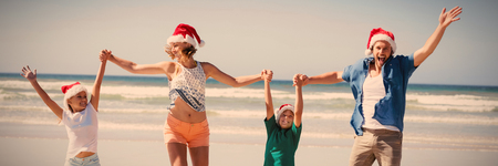 Cheerful family wearing Santa hat while jumping on shore at beach during sunny day