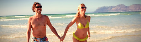 Happy young couple holding hands while running at beach during sunny day