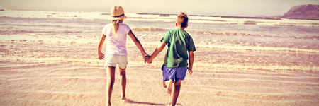 Rear view of siblings holding hands while running on shore at beach during sunny day