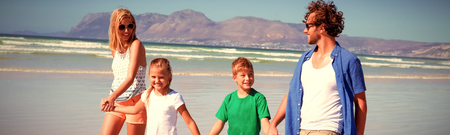 Happy family holding hands while walking together on shore at beach during sunny day