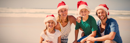 Portrait of smiling family wearing Santa hat at beach during sunny day Stock Photo