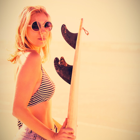 Portrait of beautiful woman holding surfboard at beach during sunny day Stock Photo