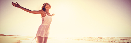 Full length of carefree woman with arms outstretched standing at beach during sunny day Stock Photo