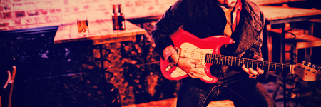 Young man playing guitar in pub