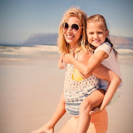 Portrait of happy mother piggybacking her daughter at beach during sunny day Stock Photo