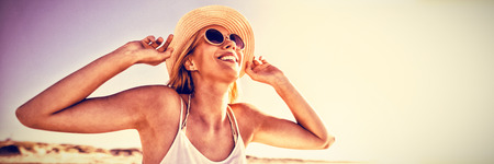 Happy woman wearing sunglasses and hat at beach during sunny day