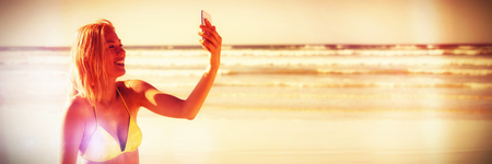 Happy young woman in yellow bikini taking selfie at beach during sunny day