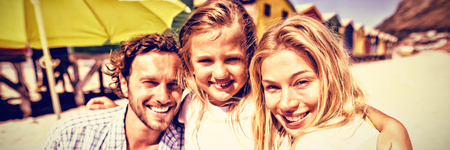 Portrait of smiling family at beach during sunny day Stock Photo