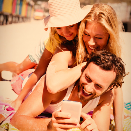 Happy family taking selfie while lying on picnic blanket at beach during sunny day Stock Photo