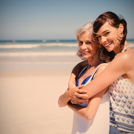 Portrait of happy woman embracing her mother at beach during sunny day