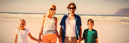 Portrait of happy family holding hands while standing together at beach during sunny day