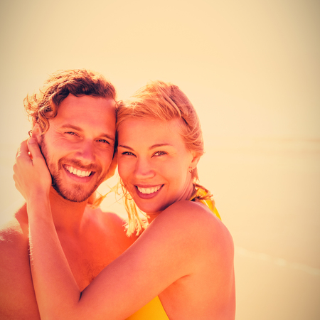 Portrait of smiling couple embracing at beach during sunny day