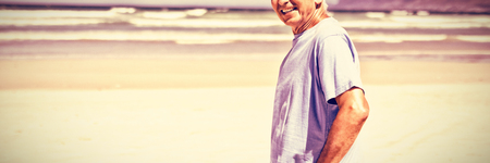 Portrait of senior man standing at beach during sunny day Stock Photo