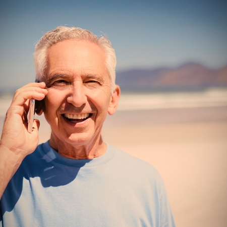 Portrait of senior man talking on mobile phone at beach during sunny day