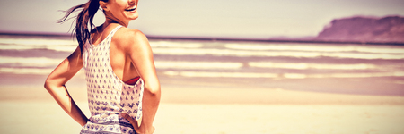 Portrait of happy woman with hands on hip standing at beach during sunny day Stock Photo