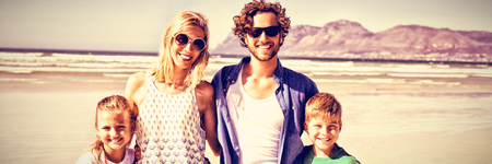 Portrait of happy family standing together at beach during sunny day Stock Photo