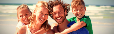 Portrait of happy family piggybacking at beach during sunny day