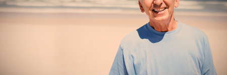 Portrait of smiling senior man at beach during sunny day