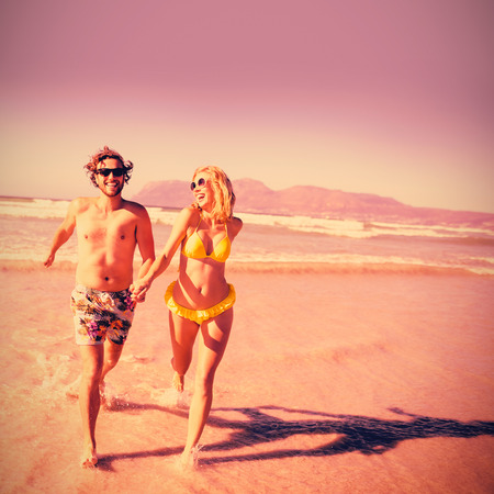 Happy couple holding hands while running on shore at beach during sunny day Stock Photo