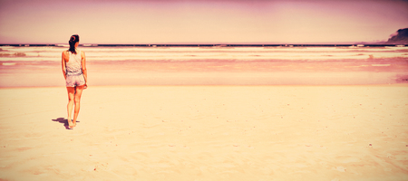 Rear view of woman walking at beach during sunny day Stock Photo