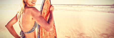 Portrait of smiling woman holding surfboard at beach during sunny day