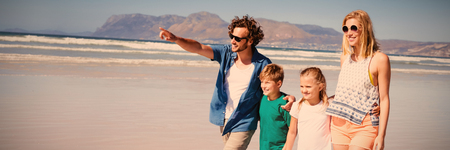 Happy man pointing away with family walking at beach during sunny day
