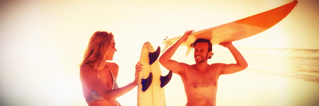Happy couple holding surfboard at beach during sunny day
