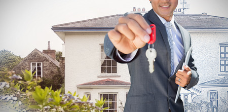 Confident estate agent standing at front door showing key against pretty house with a blue and white filter Stock Photo