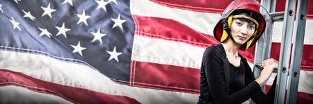 Weiblicher Architekt, der Leiter gegen weißen Hintergrund gegen Nahaufnahme einer Flagge hält Standard-Bild