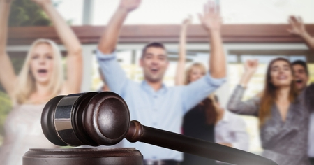 Digital composite of Gavel and people celebrating with joy
