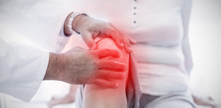 Highlighted pain against physiotherapist giving knee therapy to senior woman Stockfoto