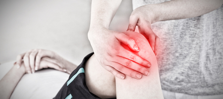 Masseuse massing the knee  against highlighted pain Stock Photo