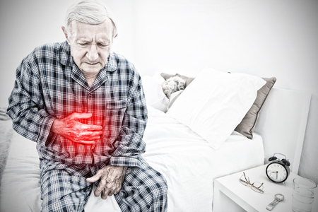 Aged man suffering with belly pain against highlighted pain