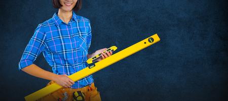 Female architect holding measuring equipment against grey background against blank blackboard in school Stock Photo