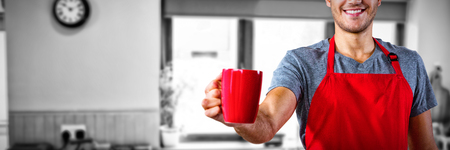 Male waiter holding coffee mug against view of kitchen