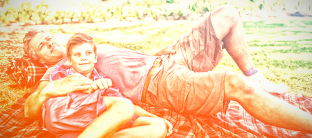 Father and son lying on picnic blanket in park on a sunny day