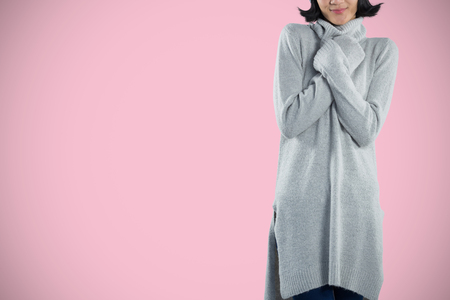 Woman in winter clothing posing against white background against pink background Stock fotó