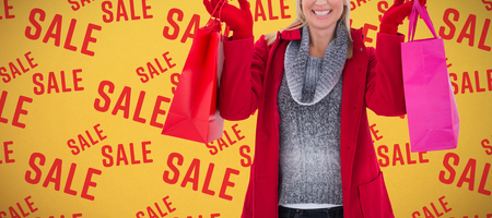 Blonde in winter clothes holding shopping bags against orange background Archivio Fotografico